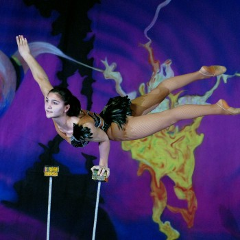 Female circus performer balancing on one hand on stilts.