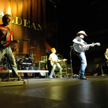 Front row shot of a country band playing guitars on stage.