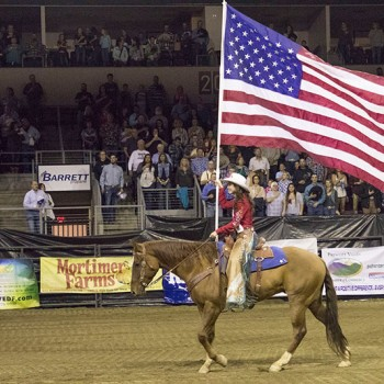 The rodeo queen is riding a brown horse and carrying an American flag.